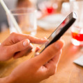 Close up of hands woman using her cell phone in restaurant
